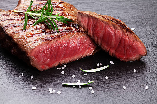 Grilled beef steak with rosemary, salt and pepper Grilled beef steak with rosemary, salt and pepper on black stone plate red meat stock pictures, royalty-free photos & images