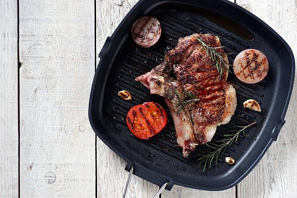 grilled beef steak with rosemary, tomato, garlic and onions - marinade für grillfleisch stock-fotos und bilder