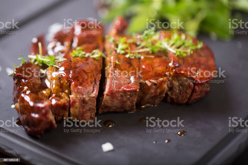 Grilled Beef Steak with sous herbs on a black plate stock photo