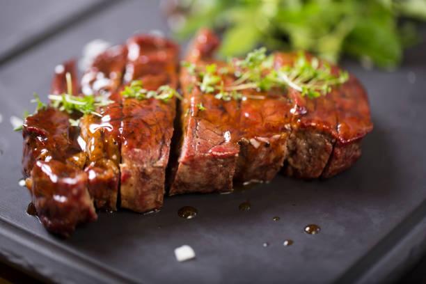 gegrilltes rindersteak mit sous kräutern auf einer schwarzen platte - steak anbraten stock-fotos und bilder