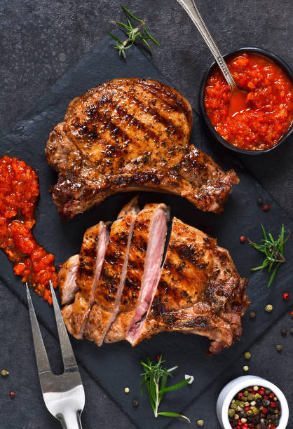 gegrilltes rindersteak mit gewürzen und tomatensauce auf einer steinplatte. - grillstein stock-fotos und bilder