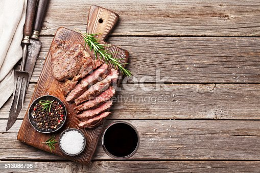 808351132 istock photo Grilled beef steak with spices on cutting board 813086798