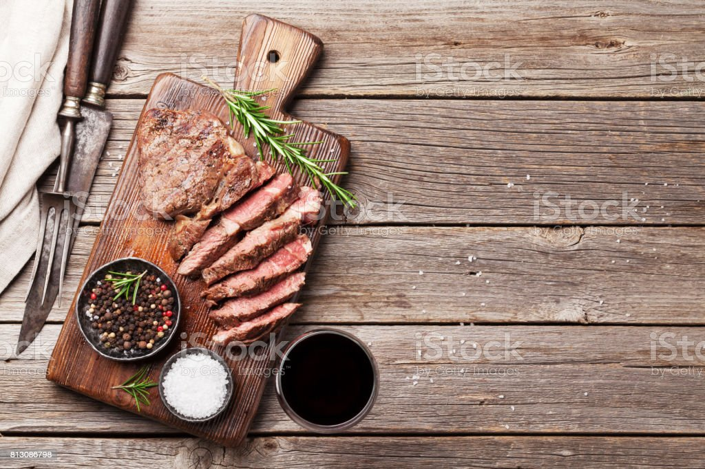 Grilled beef steak with spices on cutting board stock photo