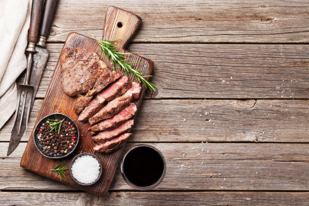 gegrilde biefstuk met kruiden op snijplank - ribeye biefstuk stockfoto's en -beelden