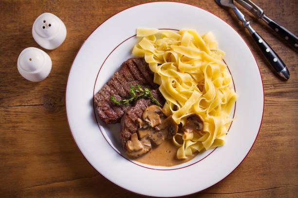 Filetes de ternera a la plancha y fideos en salsa cremosa de champiñones, adornados con tomillo en plato blanco - foto de stock