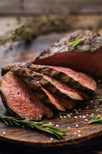 Grilled beef steaks with spices. Juicy medium Beef Rib Eye steak slices on wooden board with herbs spices and salt. Ready to eat steak with ingredients on a cutting board. beef stock pictures, royalty-free photos & images