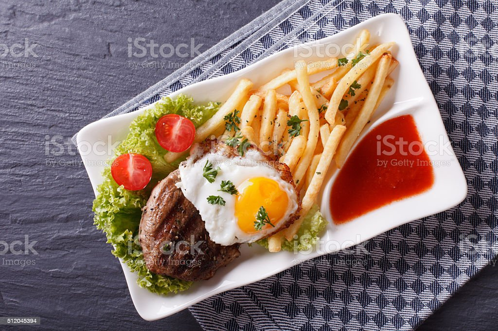 Grilled beefsteak, fried egg and French fries. horizontal top vi stock photo