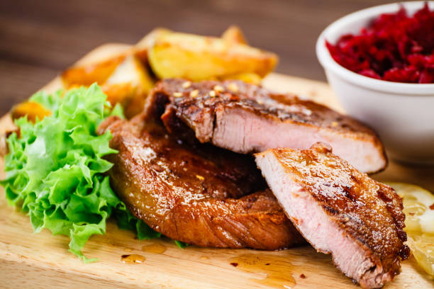 Grilled beefsteak with baked potatoes and beetroots stock photo