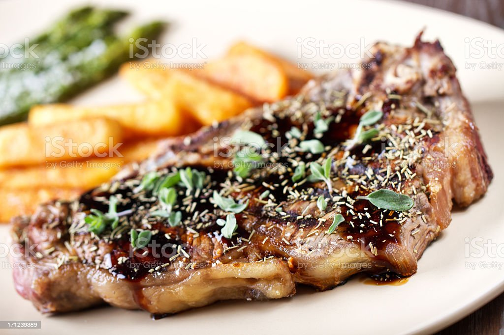 Grilled beefsteak with french fries and asparagus royalty-free stock photo