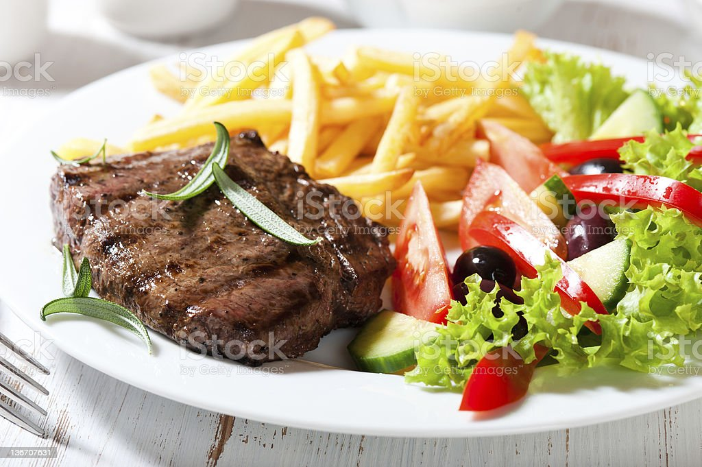 Grilled beefsteak with french fries and salad stock photo