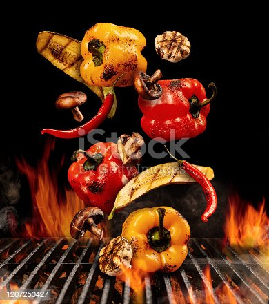 Grilled red and yellow bell pepper, zucchini, champignons, chilli and halves of garlic are falling down on black background. Bbq grill, flaming fire, charcoal and smoke. Cooking. Close up, copy space