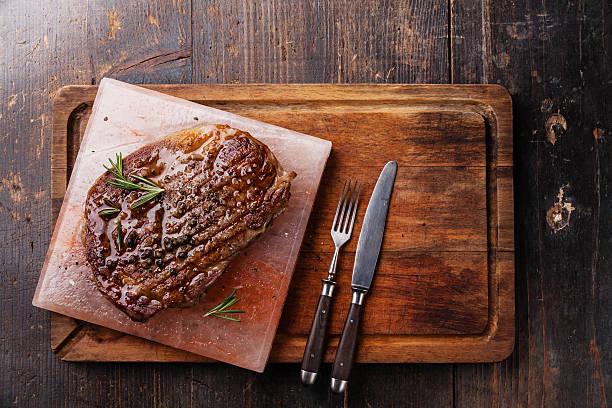 grilled black angus steak ribeye on himalayan pink salt block - vleesdelen stockfoto's en -beelden