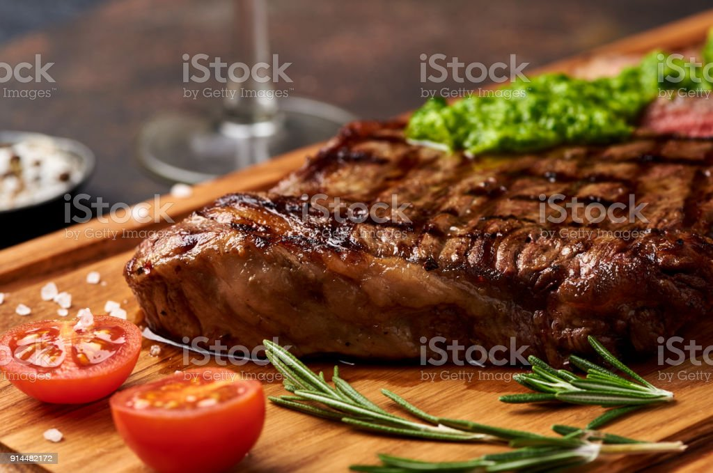 Grilled Black Angus Steak with tomatoes, garlic with chimichurri sauce on meat cutting board. stock photo