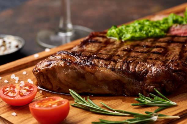 gegrilde black angus steak met tomaten, knoflook met chimichurri saus op vlees snijplank. - sirloin stockfoto's en -beelden