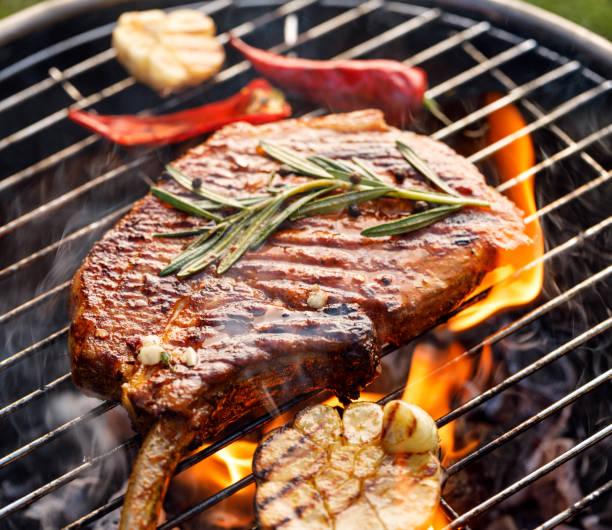gegrilde bot-in varkensvlees chop, varkensvlees steak, tomahawk in pittige marinade op een vlamende grill plat, close-up. - ribeye biefstuk stockfoto's en -beelden