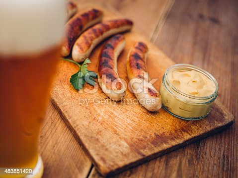 Freshly grilled bratwurst sausages on a wooden board with fresh german mustard and a pint glass of beer in the foreground