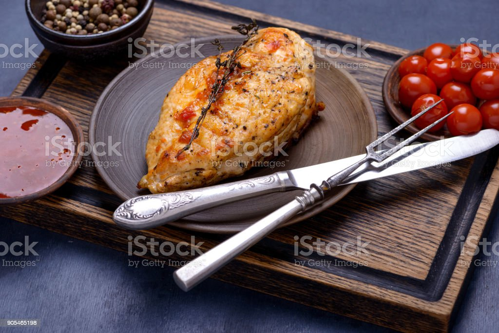 Grilled breas chicken on plate with cutlery stock photo