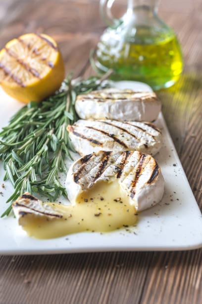 grilled camembert cheese with olive oil and rosemary - baked brie stock photos and pictures