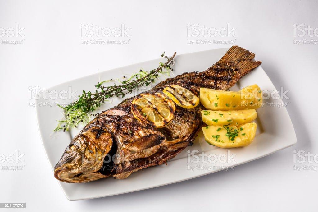 Pescados de la carpa a la plancha con patatas al romero y limón, de cerca foto de stock libre de derechos