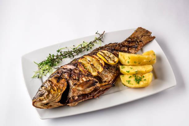 Pescados de la carpa a la plancha con patatas al romero y limón, de cerca - foto de stock