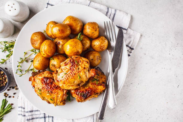 Grilled chicken and baked potatoes in white plate stock photo