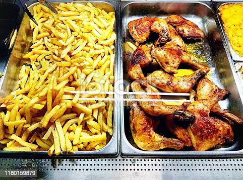 Two heated containers, one with chicken, the other with chips, ready for take away meals.