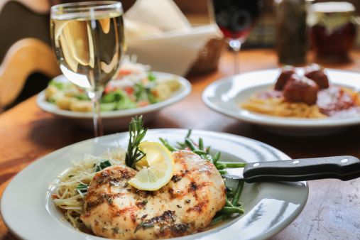 Grilled Chicken and Pasta at a table setting with red and white wine, spaghetti and meatballs and salad, a full Italian dinner