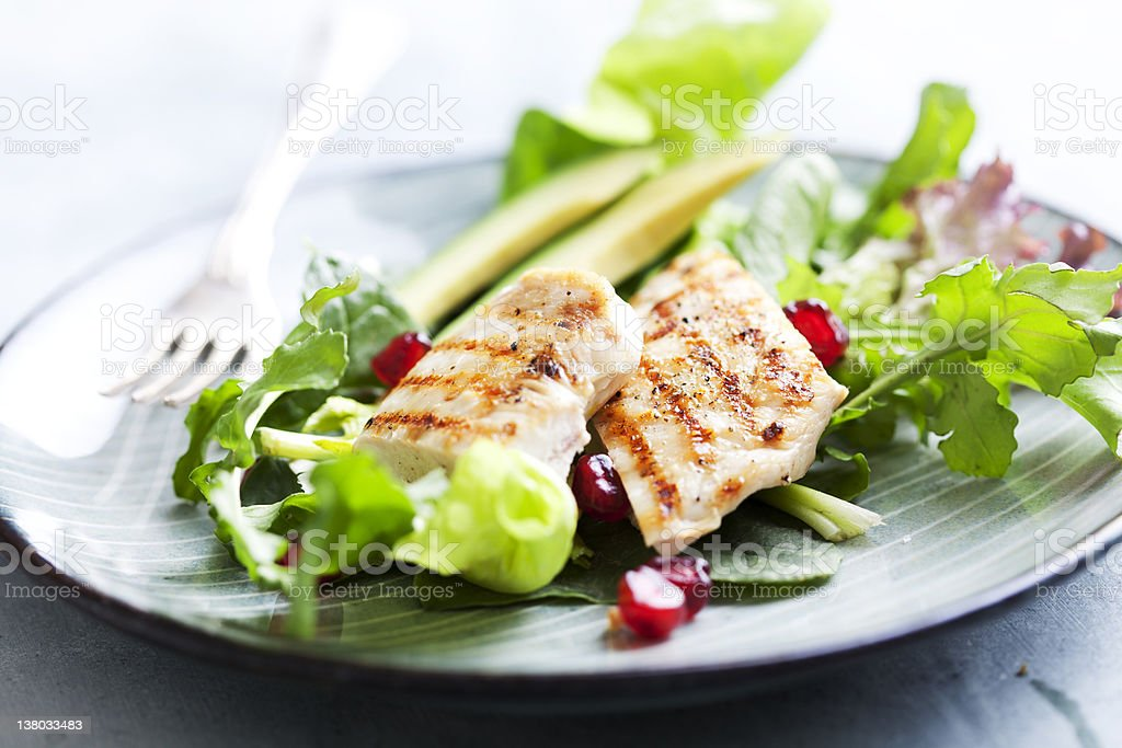Grilled chicken and salad leaves on a ceramic plate stock photo