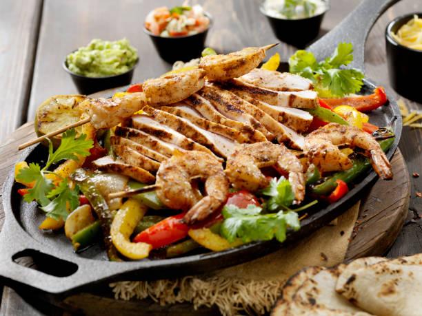 gegrilltes huhn und garnelen fajita platte - meeresfrüchte enchiladas stock-fotos und bilder