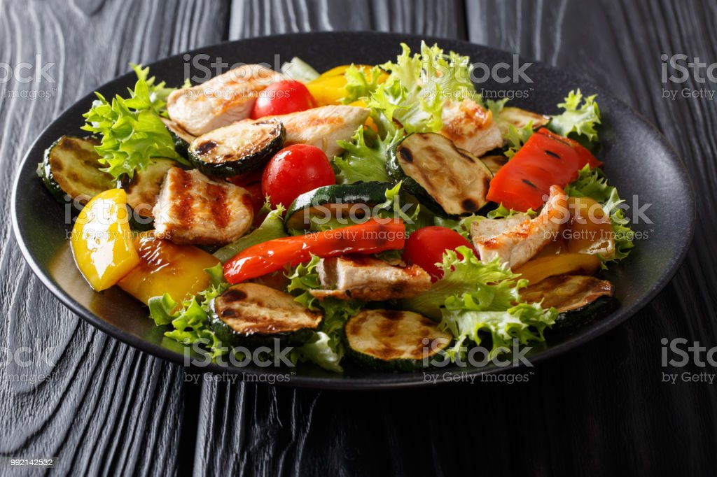 Grilled chicken breast and summer vegetables close-up on a plate. horizontal stock photo