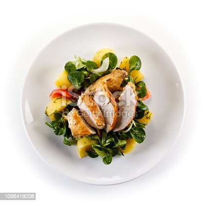 Grilled chicken breast and vegetables on white background