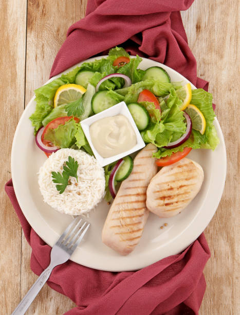 grilled chicken breast dish with salad and rice grilled chicken breast plate with salade,sauce and rice riz stock pictures, royalty-free photos & images