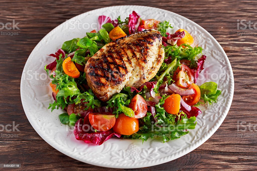 Grilled Chicken Breast fillet with fresh tomatoes vegetables salad. concept stock photo