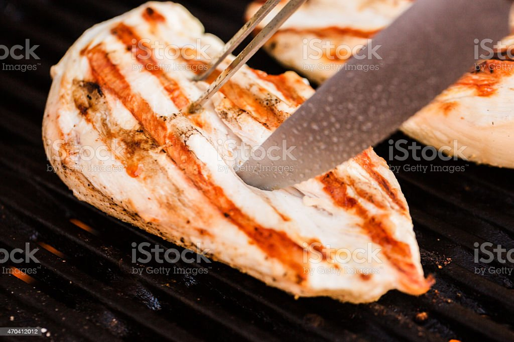 Grilled chicken breast fillets on BBQ with fork and knife stock photo