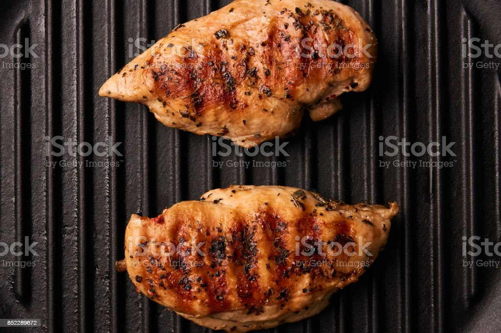 Grilled chicken breast fillets on black ribbed cooking pan stock photo