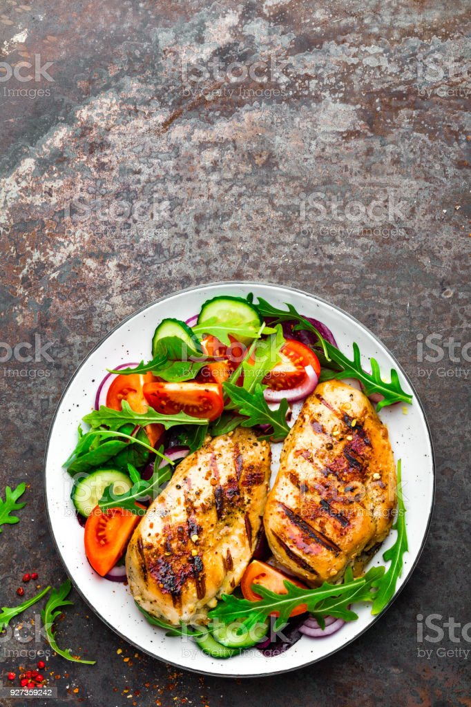 Grilled chicken breast. Fried chicken fillet and fresh vegetable salad of tomatoes, cucumbers and arugula leaves. Chicken meat with salad. Healthy food. Flat lay. Top view. Dark background Grilled chicken breast. Fried chicken fillet and fresh vegetable salad of tomatoes, cucumbers and arugula leaves. Chicken meat with salad. Healthy food. Flat lay. Top view. Dark background Above Stock Photo