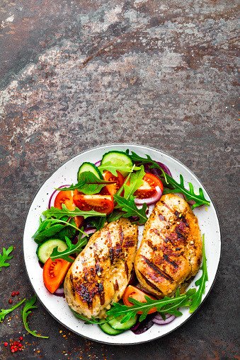 Grilled Chicken Breast Fried Chicken Fillet And Fresh Vegetable Salad Of Tomatoes Cucumbers And Arugula Leaves Chicken Meat With Salad Healthy Food Flat Lay Top View Dark Background Stock Photo - Download Image Now