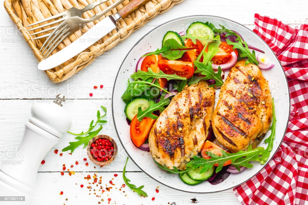 Grilled chicken breast. Fried chicken fillet and fresh vegetable salad of tomatoes, cucumbers and arugula leaves. Chicken meat salad. Healthy food. Flat lay. Top view. White background - Royalty-free Above Stock Photo