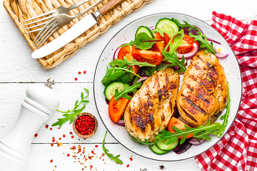 Grilled Chicken Breast Fried Chicken Fillet And Fresh Vegetable Salad Of Tomatoes Cucumbers And Arugula Leaves Chicken Meat Salad Healthy Food Flat Lay Top View White Background Stock Photo - Download Image Now