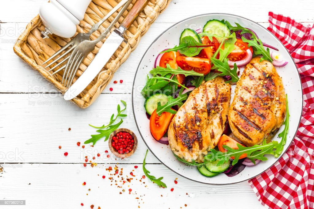 Grilled chicken breast. Fried chicken fillet and fresh vegetable salad of tomatoes, cucumbers and arugula leaves. Chicken meat salad. Healthy food. Flat lay. Top view. White background Grilled chicken breast. Fried chicken fillet and fresh vegetable salad of tomatoes, cucumbers and arugula leaves. Chicken meat salad. Healthy food. Flat lay. Top view. White background Above Stock Photo