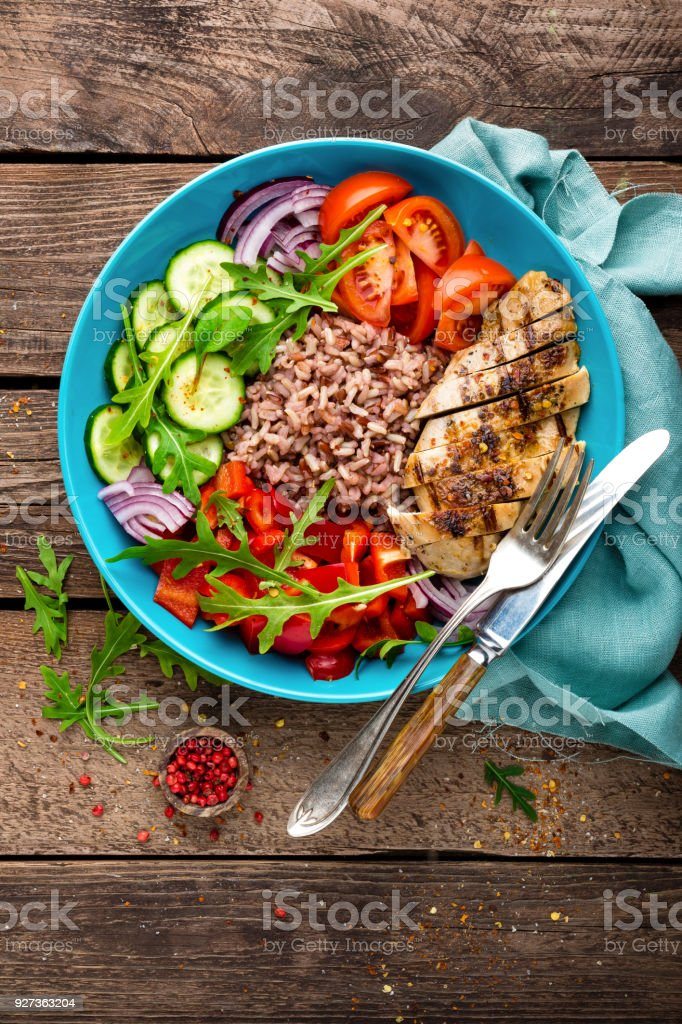 Grilled chicken breast. Fried chicken fillet and fresh vegetable salad of tomatoes, cucumbers, pepper, lettuce and arugula leaves. Chicken meat with salad. Healthy food. Flat lay. Top view. Wooden background - Royalty-free Above Stock Photo