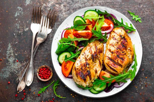 grillowana pierś z kurczaka. smażony filet z kurczaka i sałatka ze świeżych warzyw z pomidorów, ogórków i liści rukoli. mięso z kurczaka z sałatką. zdrowa żywność. płaski lay. widok z góry. ciemne tło - kurczak zdjęcia i obrazy z banku zdjęć