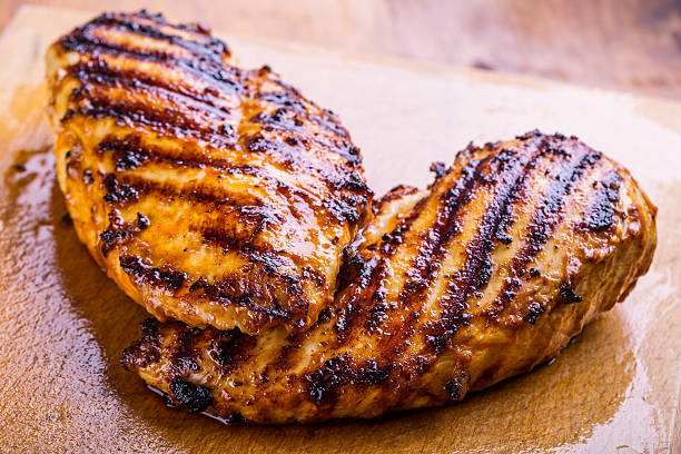 Grilled chicken breast in different variations Grilled chicken breast in different variations with cherry tomatoes, green French beans, garlic, herbs, cut lemon on a wooden board or teflon pan. Traditional cuisine. Grill kitchen. grilled chicken breast stock pictures, royalty-free photos & images