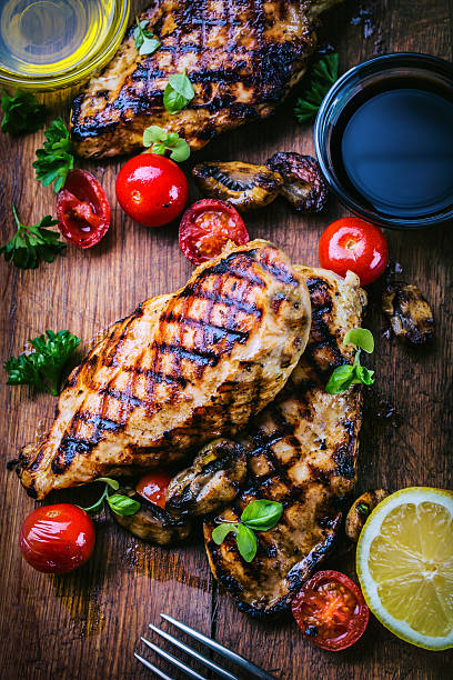 Grilled chicken breast in different variations. Traditional cuisine. Grill kitchen Grilled chicken breast in different variations with cherry tomatoes,  mushrooms, herbs, cut lemon on a wooden board or teflon pan. Traditional cuisine. Grill kitchen. grilled chicken breast stock pictures, royalty-free photos & images