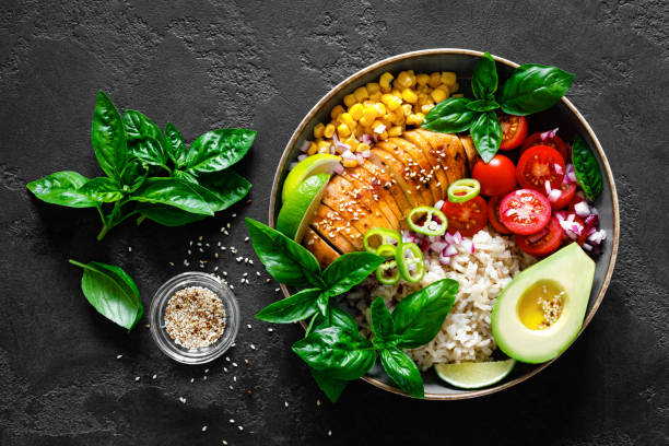 Grilled chicken breast lunch bowl with fresh tomato, avocado, corn, red onion, rice and basil stock photo