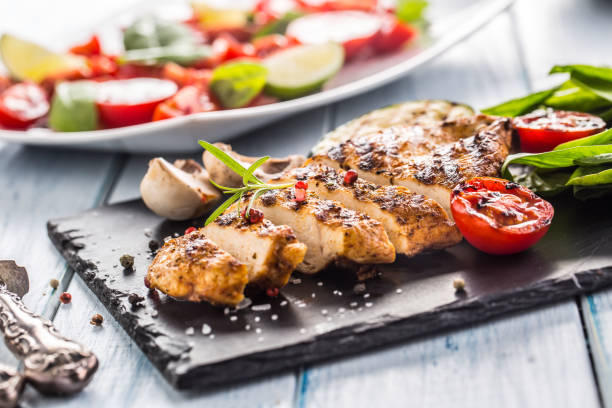 Grilled chicken breast on slate board herb spinach tomatoes and other vegetable. Grilled chicken breast on slate board herb spinach tomatoes and other vegetable. grilled chicken breast stock pictures, royalty-free photos & images