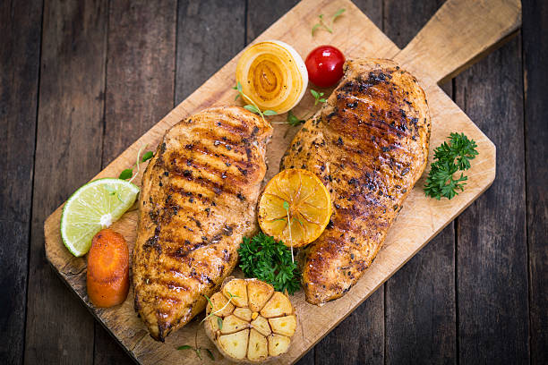 Grilled chicken breast on the cutting board Grilled chicken breast on the cutting board  grilled chicken breast stock pictures, royalty-free photos & images