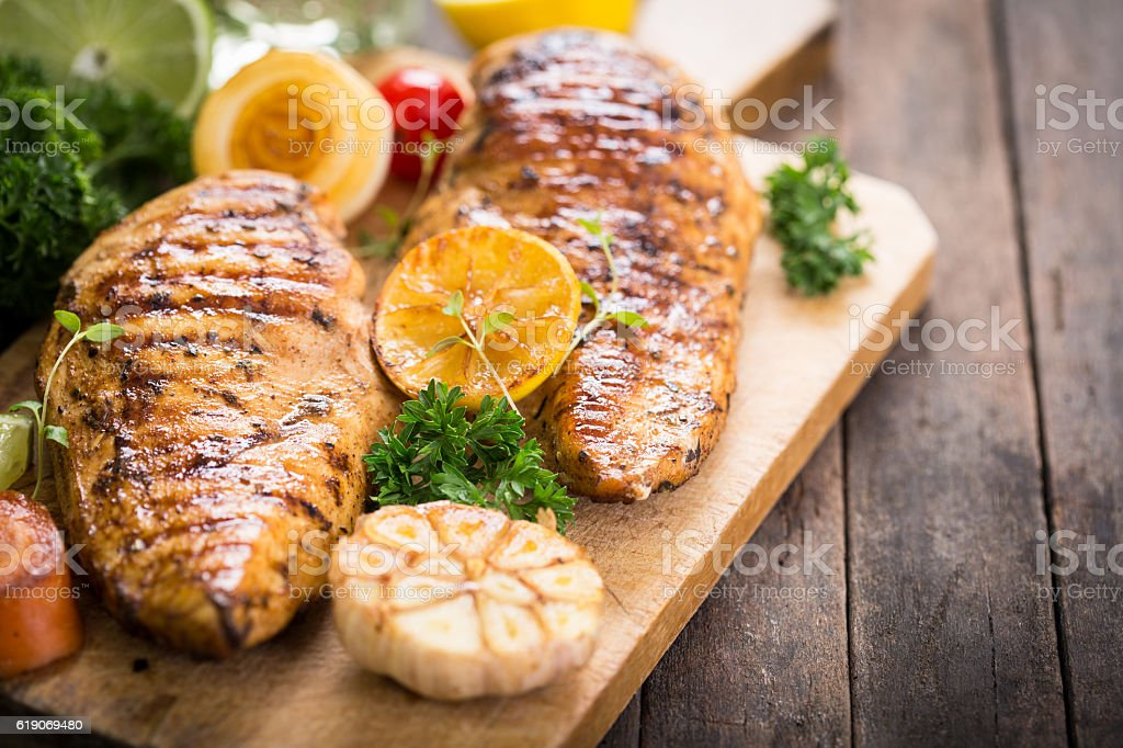 Grilled chicken breast on the cutting board stock photo