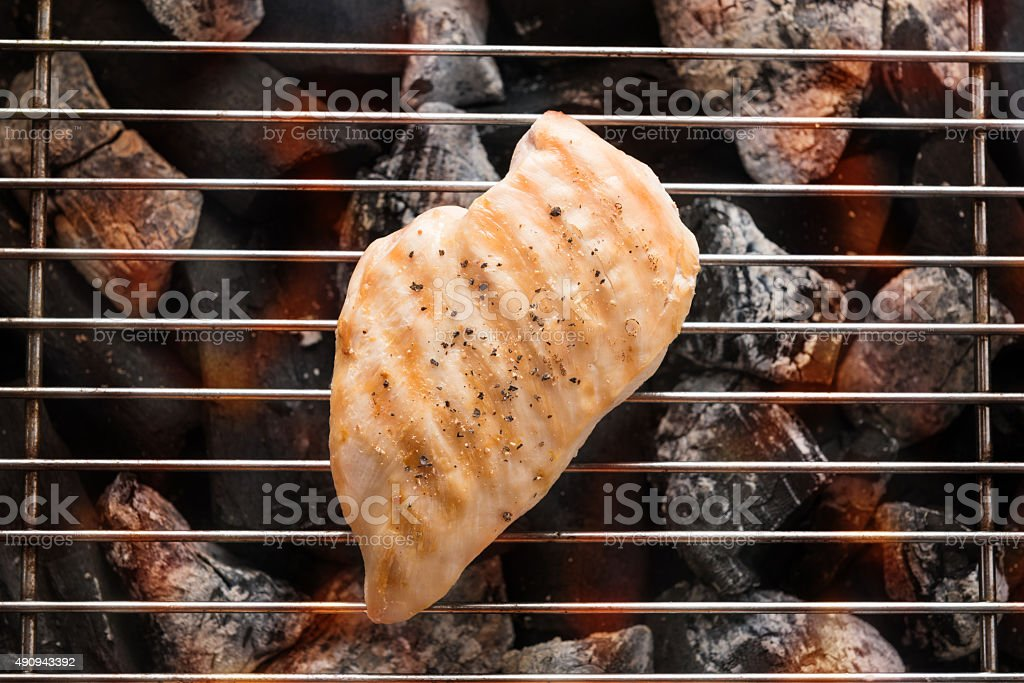 Grilled chicken breast on the flaming grill stock photo