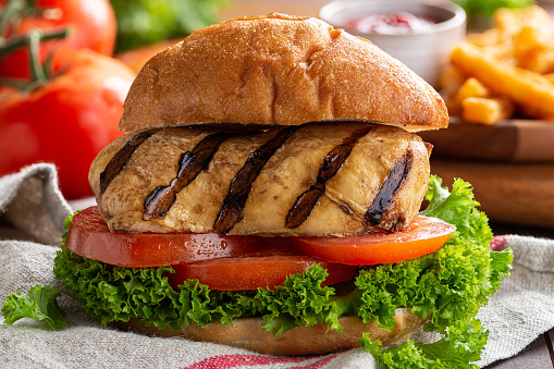 Closeup of a healthy grilled chicken breast sandwich with tomatoes and lettuce on a bun
